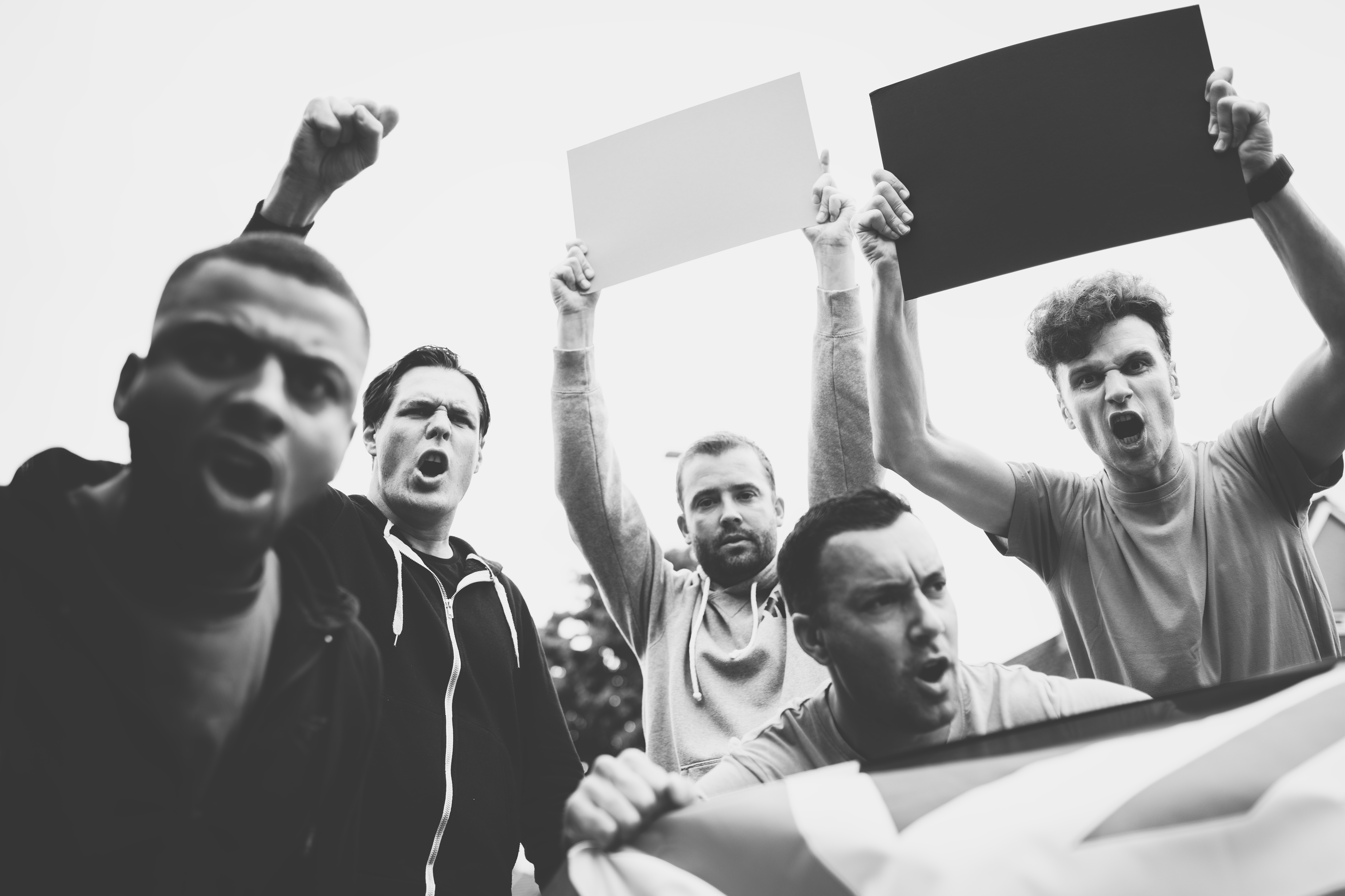 Group of angry men showing a UK flag and blank boards shouting during a protest